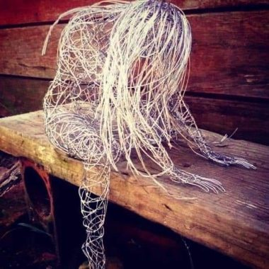 Sculpture by Simone Wojciechowski / Parkinson's News Today / metal wire sculpture of a woman sitting and leaning over. her hair covers her face.